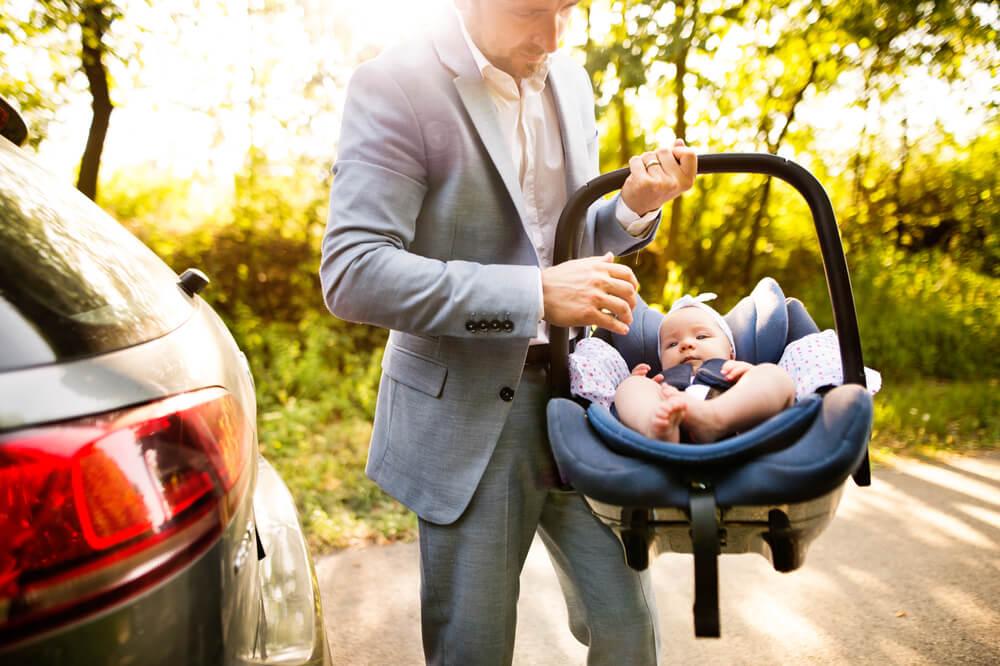 アメリカで新生児用のチャイルドシートを持つ男性