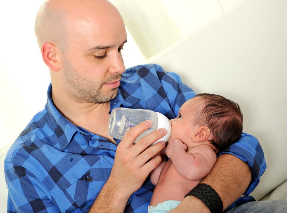 搾乳したミルクを赤ちゃんに飲ませている父親