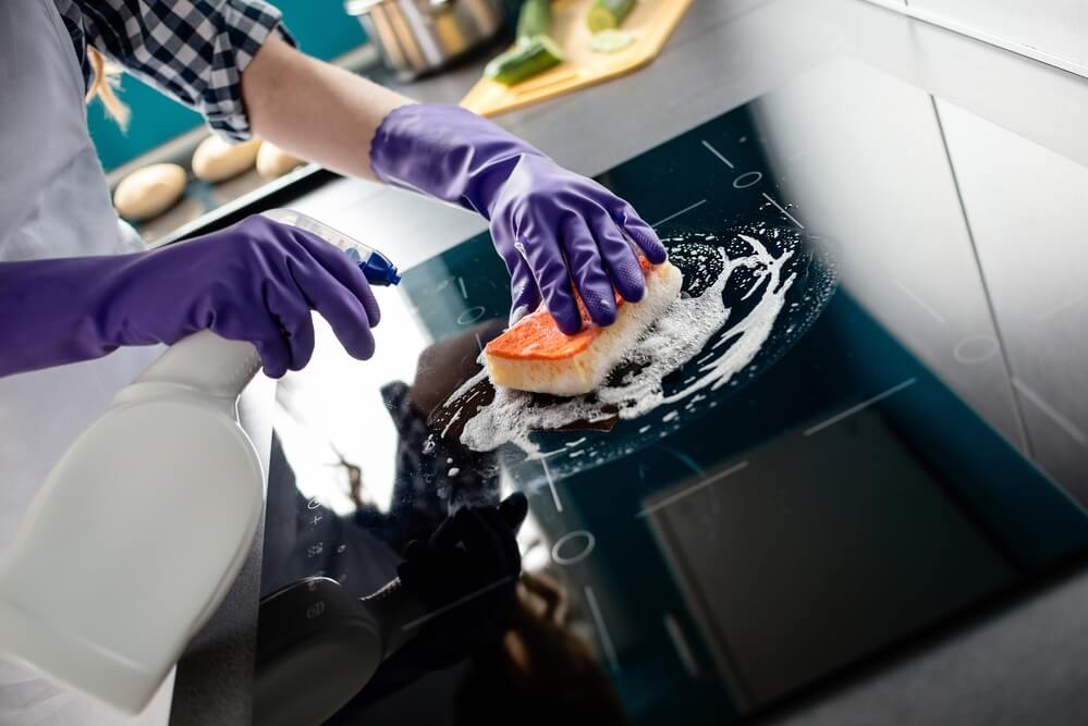 キッチンの掃除手順に従って掃除をする女性